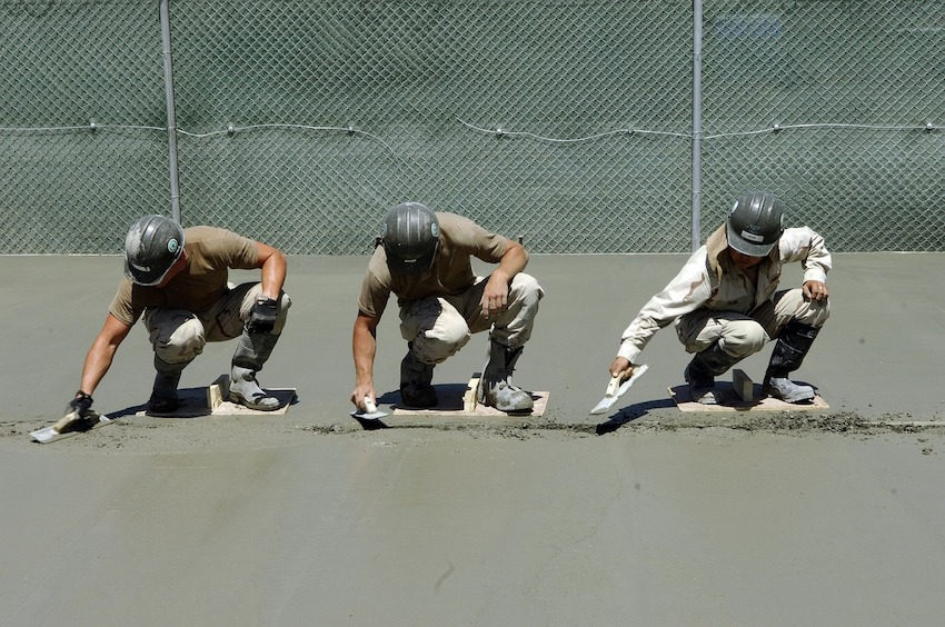 wide shot of three men pouring concrete