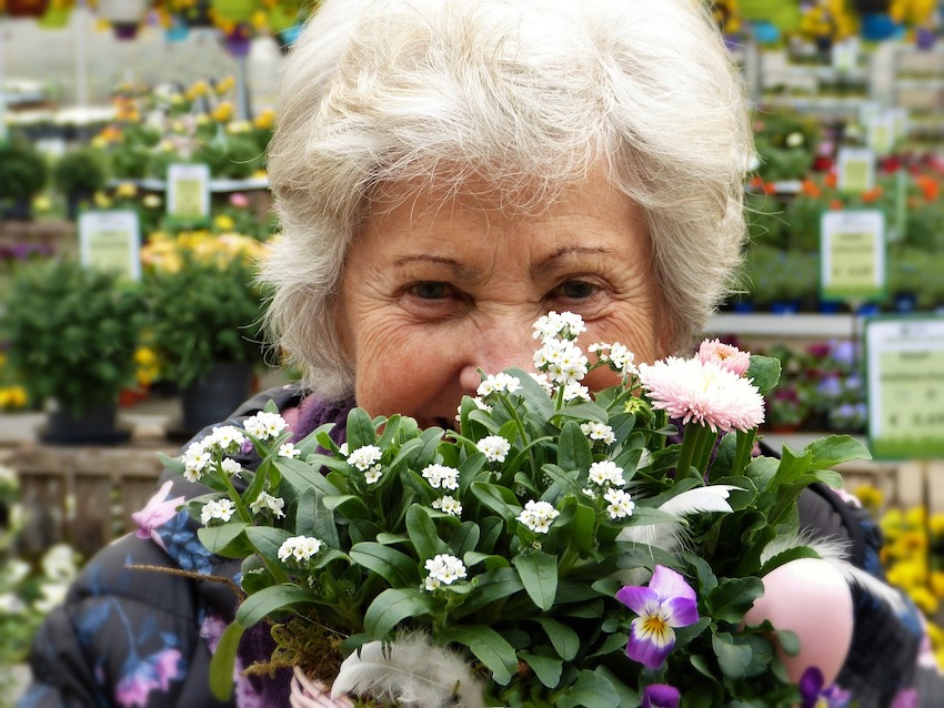 elderly woman holding flowers and smiling
